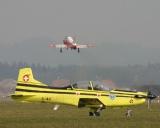 im Vordergrund eine PC-9 hinten startet eine Hawk